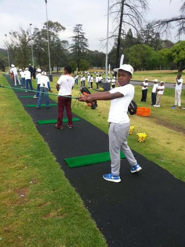Young kids learn to play golf at the hands of Andrew Mlangeni
